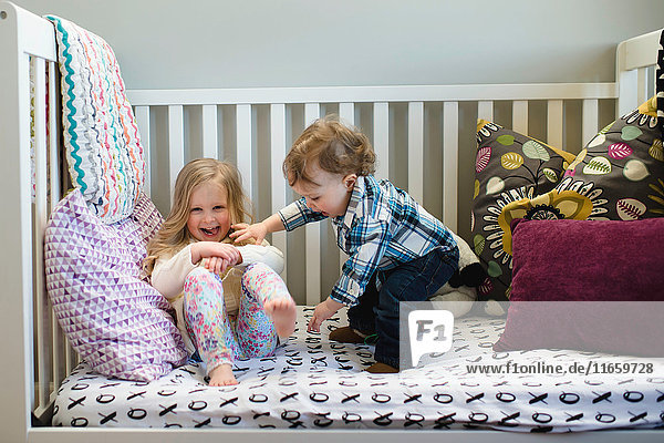 Male toddler and sister playing on day bed