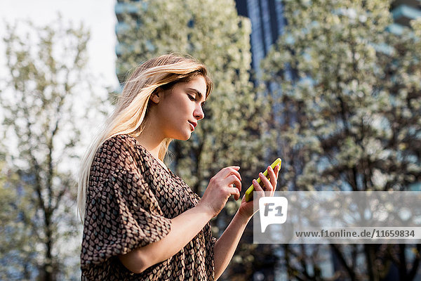 Young woman looking at smartphone in city
