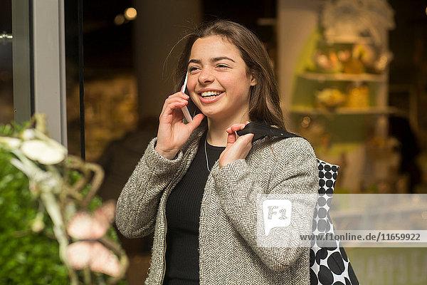 Junge Frau telefoniert mit einem Smartphone durch ein Schaufenster