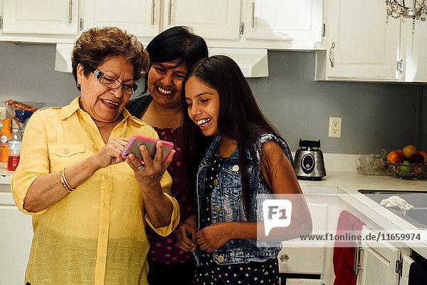 Mehrgenerationen-Familie sieht Smartphone lächelnd an