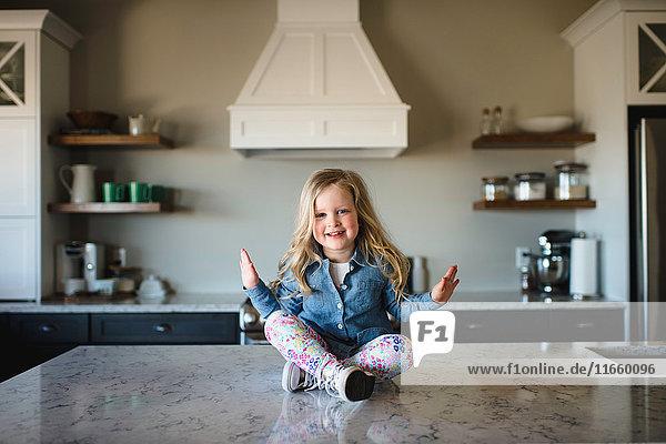 Porträt eines Mädchens  das im Schneidersitz auf dem Küchentisch sitzt