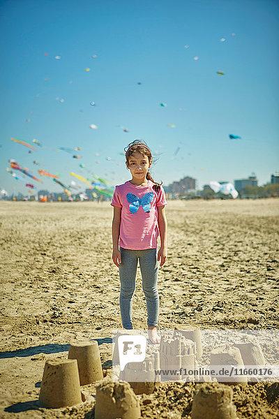 Porträt eines jungen Mädchens  das hinter Sandburgen am Strand steht  Rimini  Italien