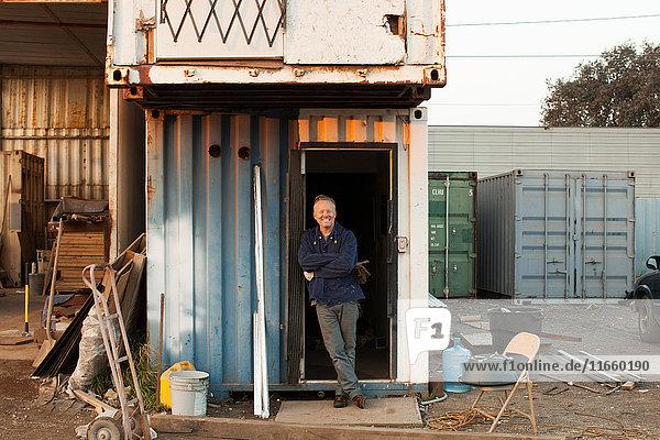 An die Tür einer Wellblechhütte gelehnte Bauarbeiter