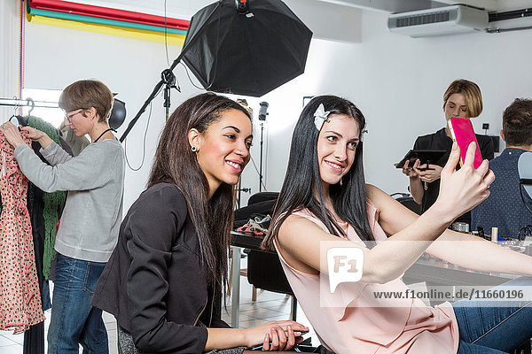 Two fashion models taking smartphone selfie in photographers studio