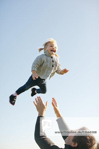 Weibliches Kleinkind vom Vater in die Luft gegen den blauen Himmel geworfen
