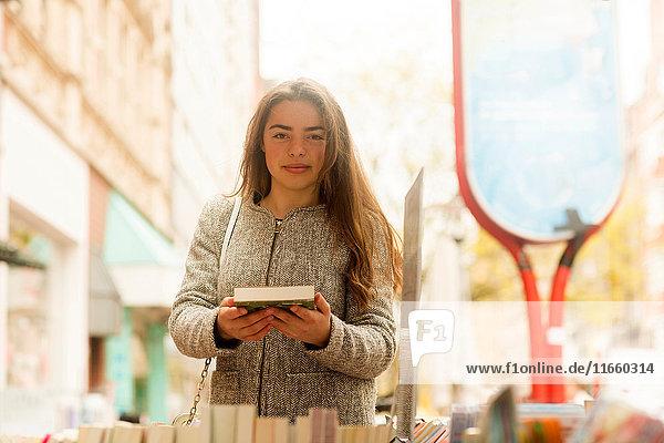 Porträt einer jungen Frau mit Buch in der Hand am Marktstand