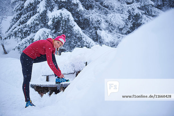 Porträt einer Läuferin beim Schnürsenkelbinden auf einer Parkbank im Tiefschnee  Gstaad  Schweiz