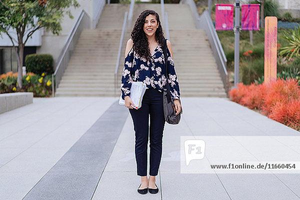 Porträt einer jungen Frau  die im Freien steht und Tasche und Papiere hält