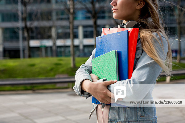 Young woman  walking outdoors  carrying document files and notebook  mid section