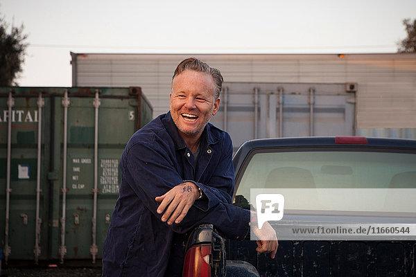 Mann lehnt lächelnd am Lastwagen