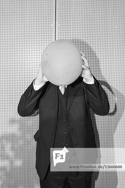 Mann im Anzug  Gesicht durch Ballon verdeckt