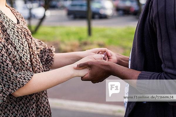 Mittelteil eines romantischen jungen Paares  das in der Stadt Händchen hält.