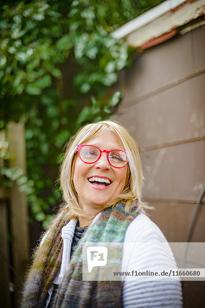 Woman laughing by garden shed