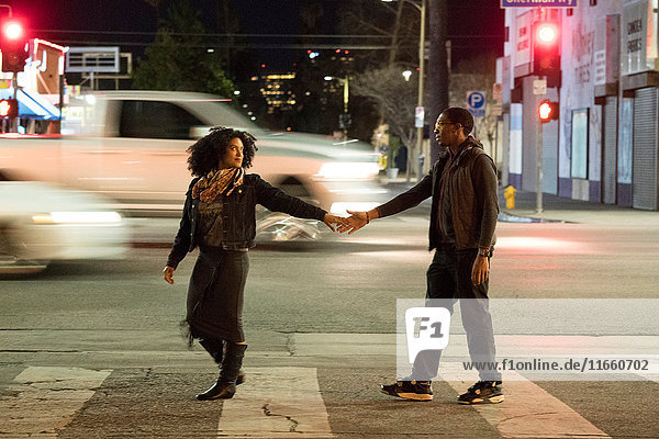 Paar hält Hände auf einem Fußgängerüberweg  Los Angeles  Kalifornien  USA