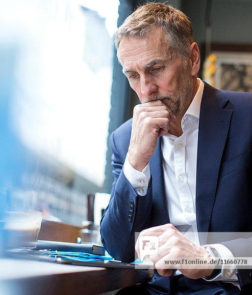 Erwachsener Geschäftsmann mit digitalem Tablett im Restaurant-Fenstersitz
