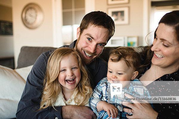 Porträt mittelgroßer Eltern mit Mädchen und Junge zusammen auf dem Sofa