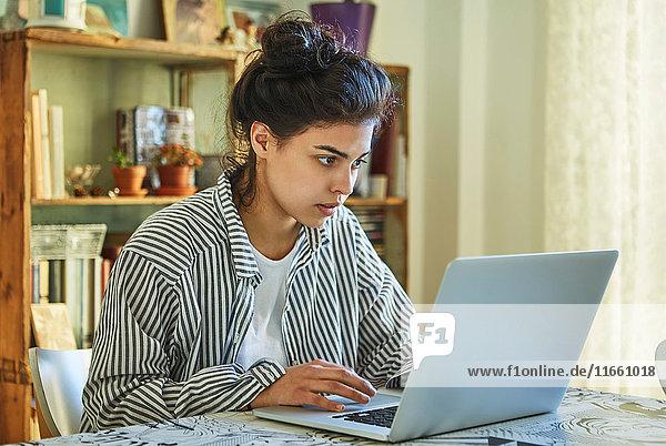Mädchen sitzt am Tisch und schaut auf den Laptop