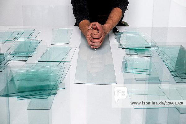 Männerhände mit Glasschneider auf Glasscheibe an der Werkbank