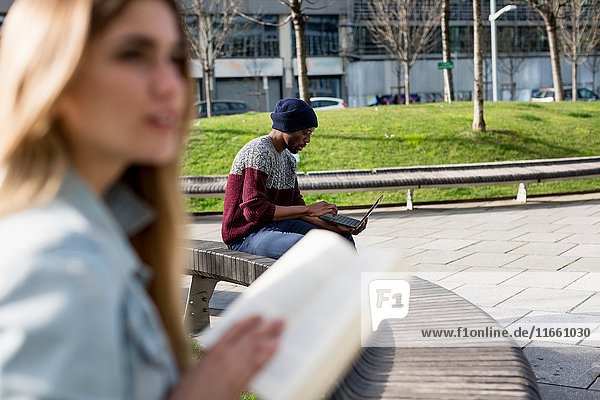 Young man and woman sitting apart on bench  man using laptop  woman holding book