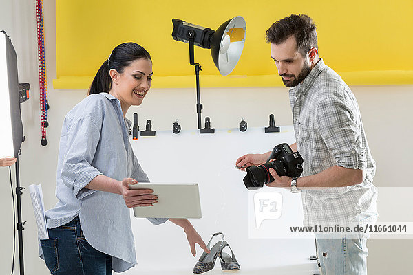 Stylist and photographer looking at digital tablet in photography studio