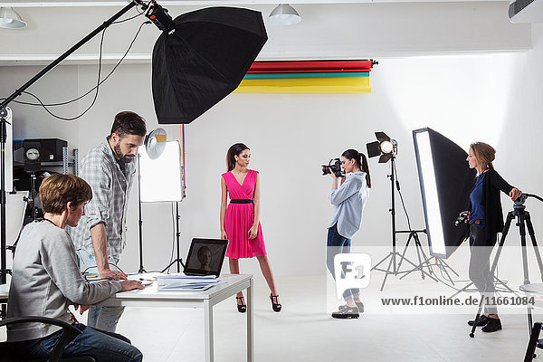 Photographer photographing fashion model in white backdrop photography studio shoot