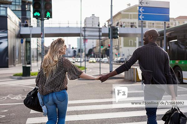 Rückansicht eines jungen Paares  das an einem Fußgängerüberweg in der Stadt Händchen hält.