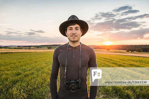 Portrait of mid adult man  standing in field  SLR camera around neck  Neulingen  Baden-Württemberg  Germany