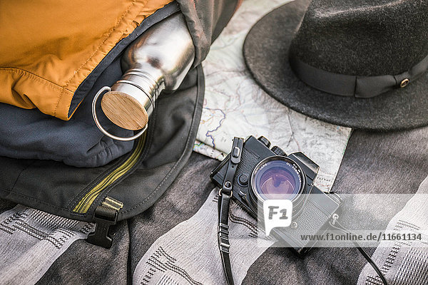 Still life of blanker  SLR camera  drinking flask and hat