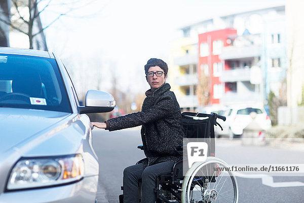 Woman in wheelchair  opening car door