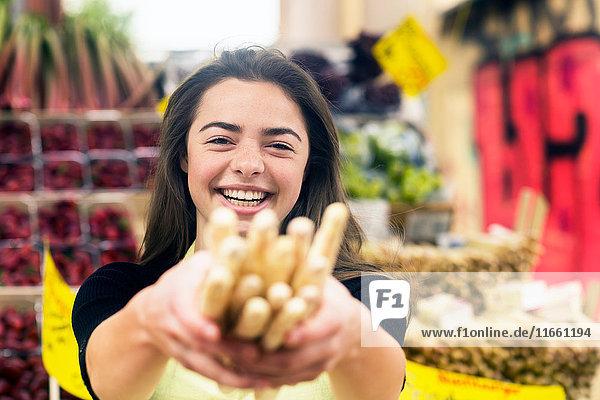 Porträt einer jungen weiblichen Standhändlerin mit einem Bündel Brotstangen