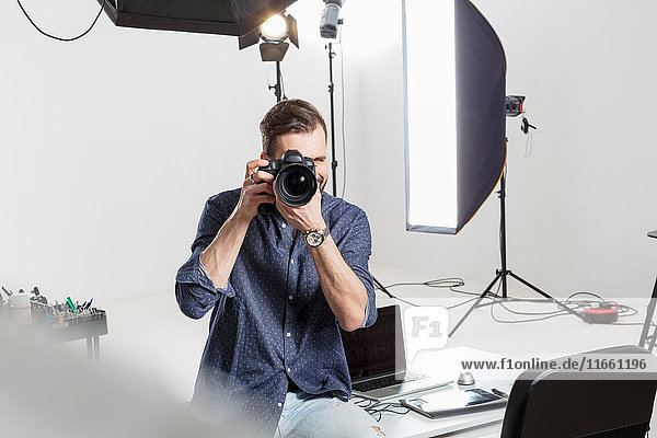 Male photographer testing focus on digital SLR in photography studio