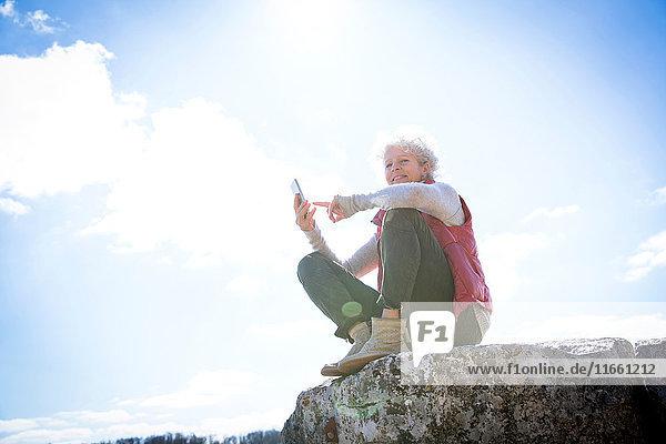 Frau sitzt auf einem Felsen und hält ein Smartphone in der Hand und lächelt  Bruniquel  Frankreich