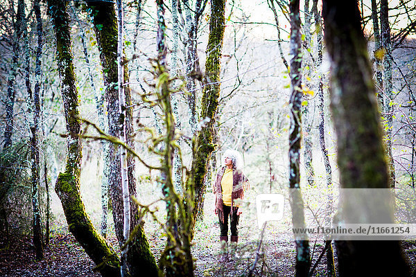 Reife Frau beim Waldspaziergang