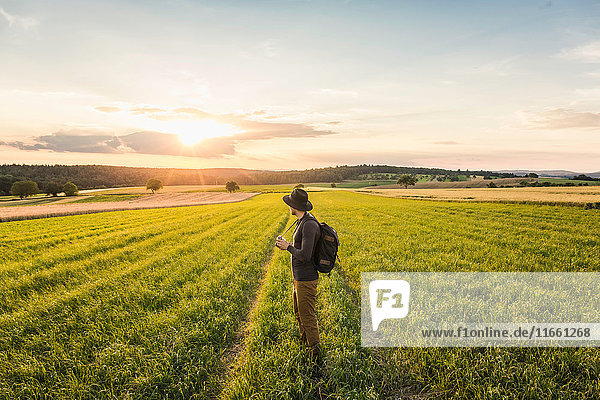 Mid adult man  standing in field  holding SLR camera  looking at view  Neulingen  Baden-Württemberg  Germany