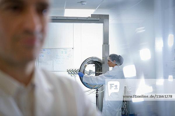 Beschäftigte in Pillenbeschichtungsanlage in pharmazeutischer Fabrik
