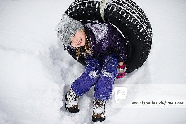 Overhead portrait of girl on tire swing in snow