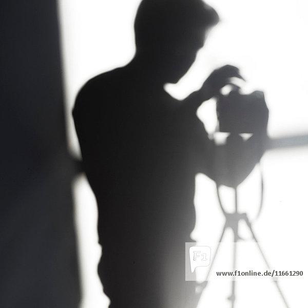 Schatten des Fotografen mit Kamera auf Stativ