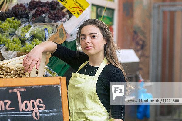 Porträt einer jungen weiblichen Obst- und Gemüsestandhändlerin