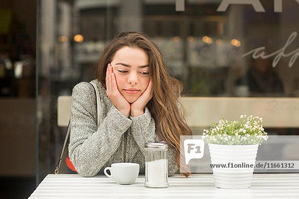 Junge Frau mit Kinn in Händen im Straßencafé