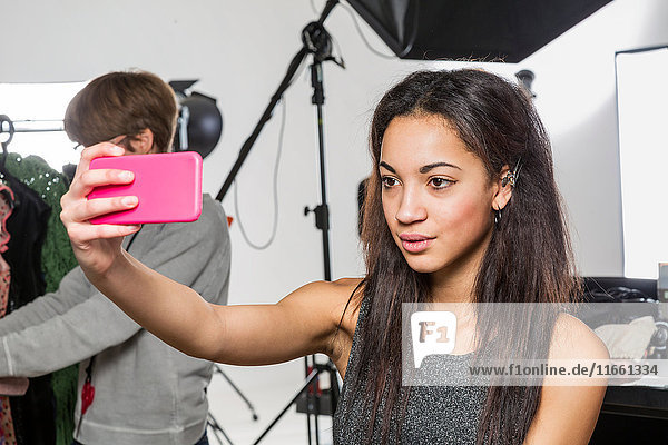 Young female fashion model taking smartphone selfie in photographers studio