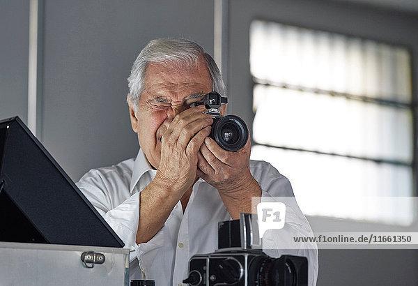 Älterer Mann schaut durch die Kamera