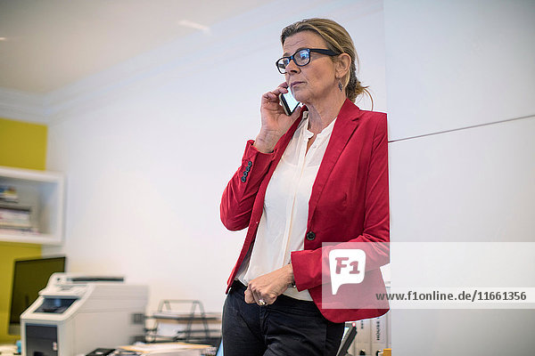 Businesswoman in office using smartphone