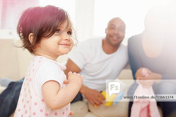 Kleines Mädchen wackelt im Wohnzimmer  während die Eltern zusehen