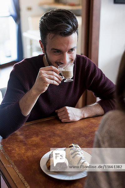 Young couple sitting at table  drinking coffee  pastries on table  focus on man