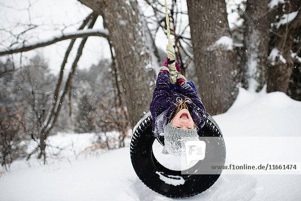 Girl upside down on tire swing in snow