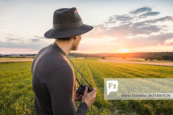 Portrait of mid adult man  standing in field  holding SLR camera  looking at view  Neulingen  Baden-Württemberg  Germany