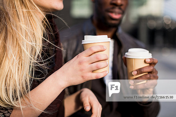 Cropped shot of young couple holding takeaway coffee in city