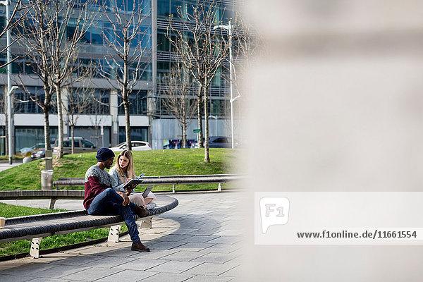 Junger Mann und Frau auf der Bank sitzend  studierend  mit digitalem Tablett und Laptop