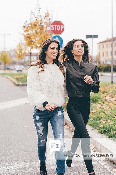 Zwillingsschwestern,  die im Freien gehen,  lächelnd