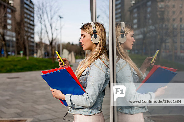 Young woman  outdoors  leaning against window  wearing headphones  holding smartphone and document files